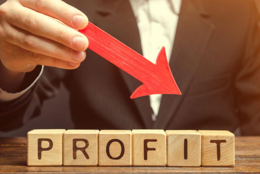 A businessman holds a downward pointing red arrow over wooden blocks which spell out the word profit. Lost profit and lost business value are both ways of calculating economic damages for commercial litigation.