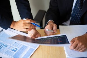 A business owner and a business valuation expert witness go over profit and value data to prepare for a case.