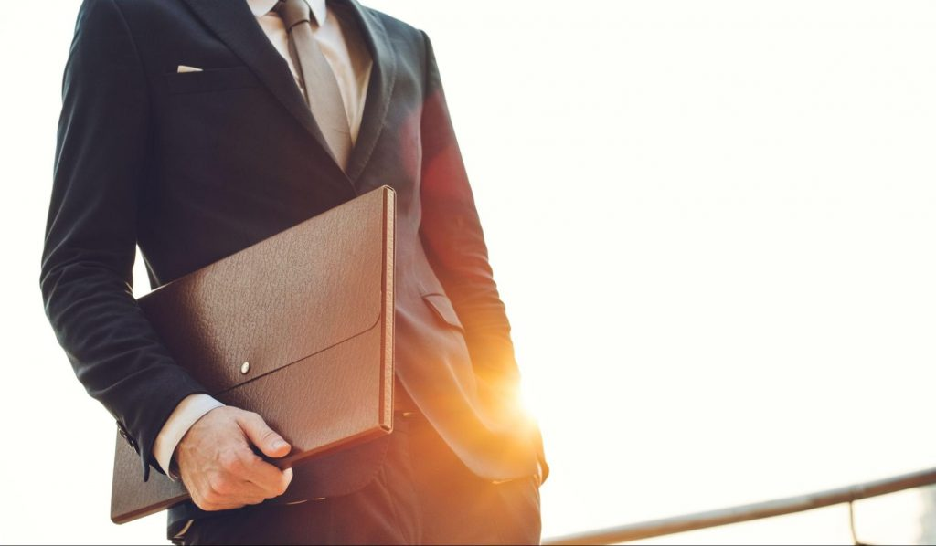 Businessman holding briefcase at sunset.